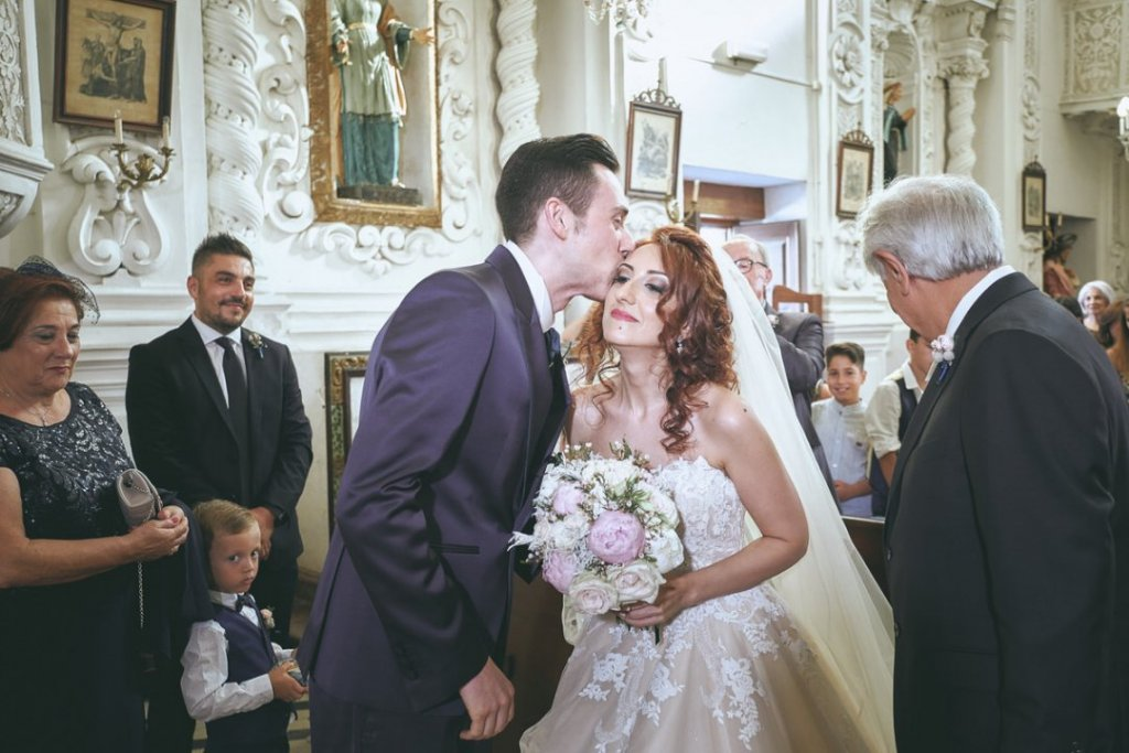 groom kiss bride afetr first look in varò church in taormina