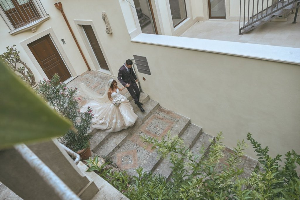 groom and bride goes down the stairs of varo varò church in taormina