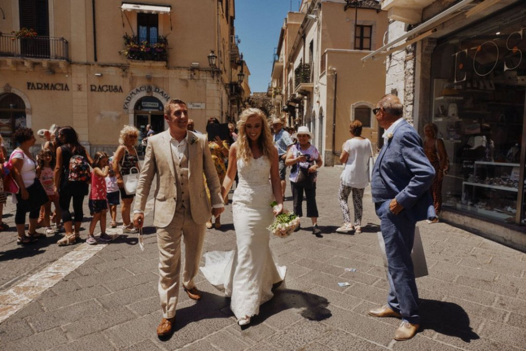 bride and groom in taormina walking in umberto road in taormina