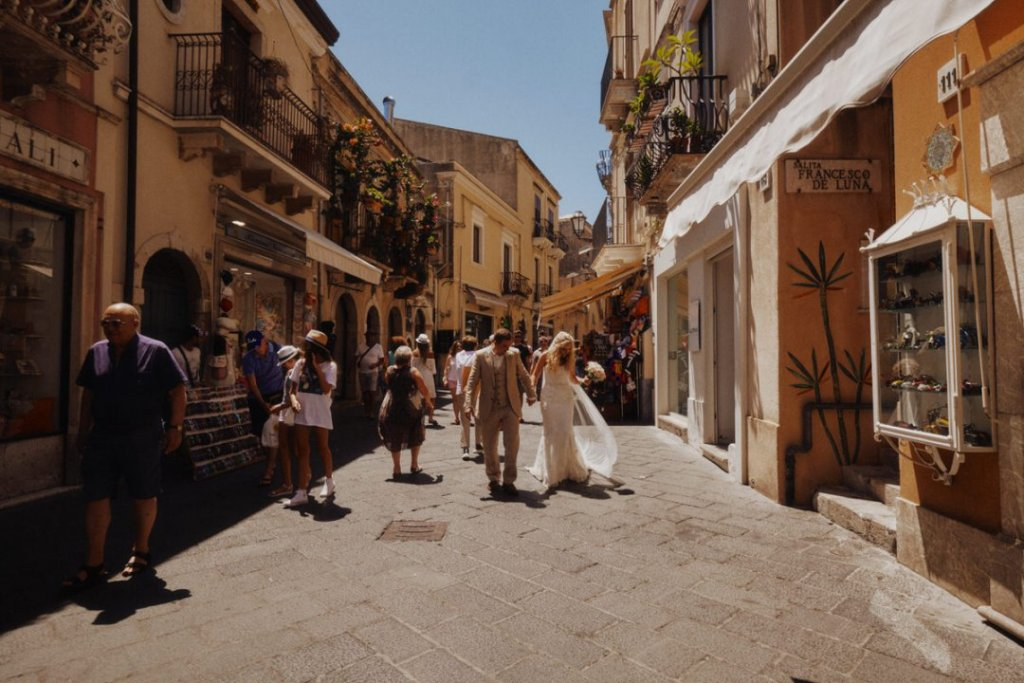 bride and groom walking in umberto road in taormina after wedding