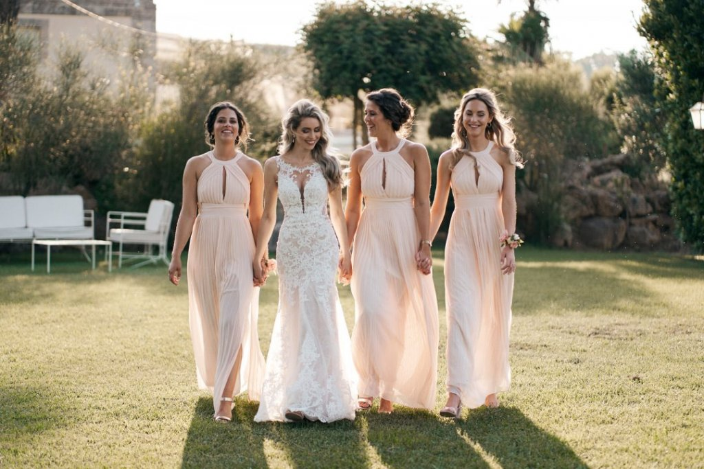 bride and bridesmaids walking in the green grass after getting married in sicily
