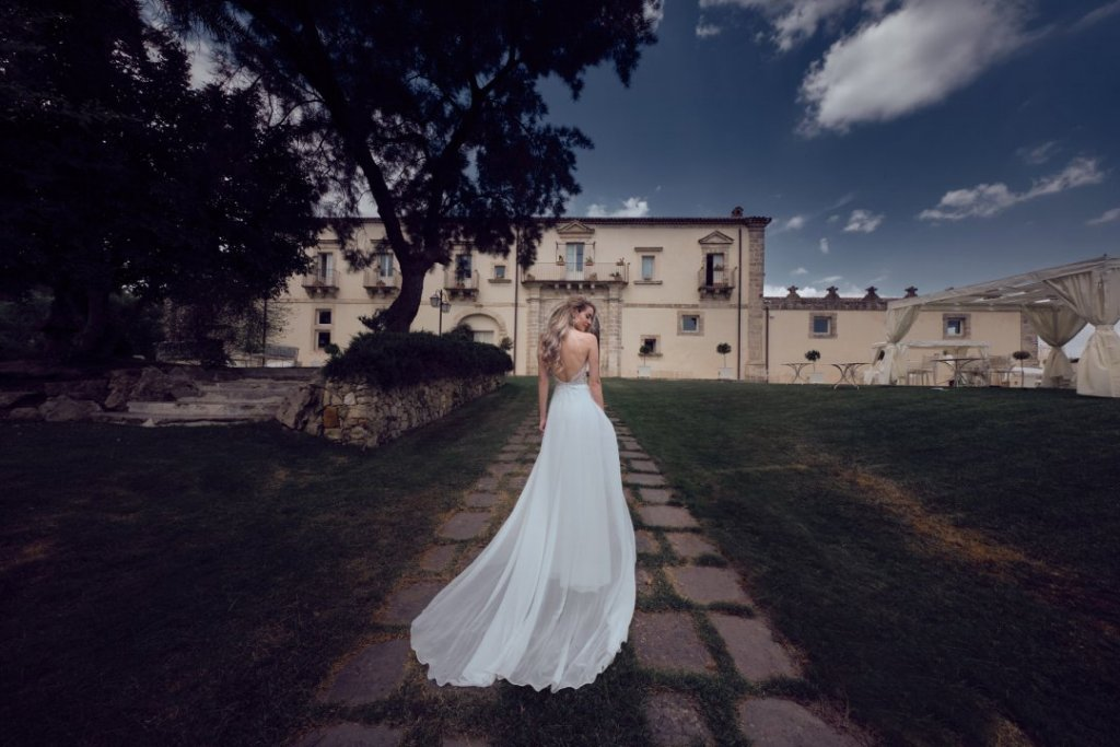 Lucienne in the green grass after getting wedding in sicily